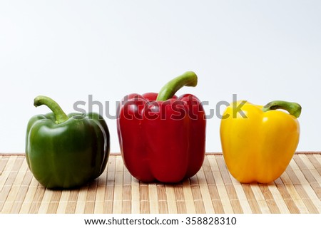 red yellow green bell peppers (capsicum) on bambo mat with white isolated  background - stock photo