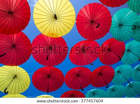 Red, yellow , turquoise umbrellas , which are suspended in the air on the street
