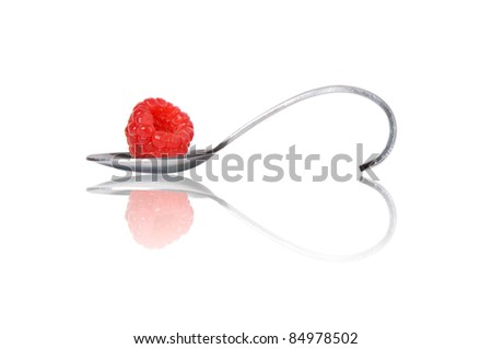 redberry on curved spoon with reflection make heart shape isolated on white