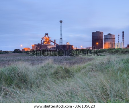 REDCAR, TEESSIDE, UNITED KINGDOM - OCTOBER 14 2015. Marshland bordering the furnace buildings of Teesside steelworks, taken on the night before the ovens were allowed to cool. Wind blurring foreground