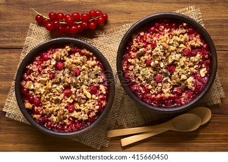 Redcurrant crumble or crisp with oatmeal and walnut on top baked in rustic bowls, photographed overhead on dark wood with natural light (Selective Focus, Focus on the top of the crumbles) - stock photo