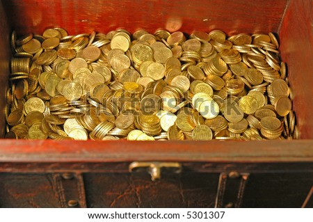 Reddish brown leather and wood treasure chest with gold colored coins (10 euro cent pieces) inside...Focus on the money inside - stock photo