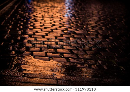 Reddish orange reflection of sunset on a cobble stoned street on a rainy day with rain drops falling on a puddle. Abstract pattern of squares made by reflection on cobblestones
