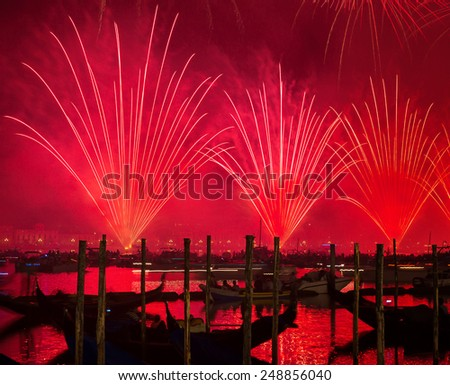 Redentore holiday, Redeemer festival of fireworks, beautiful red salute over water, traditional celebration, tourism and travel to Venice, Italy - stock photo