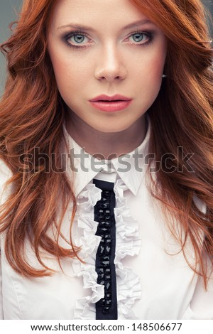 Redhead business woman closeup face portrait over gray background