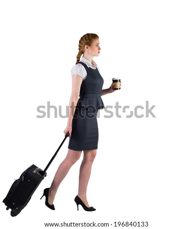 Redhead businesswoman pulling her suitcase holding coffee on white background