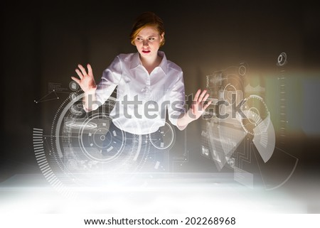 Redhead businesswoman using interactive desk against bright light in a curved room - stock photo