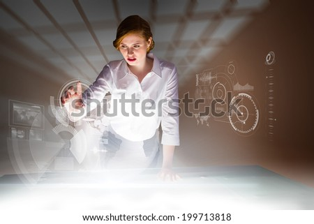 Redhead businesswoman using interactive desk against room with windows at ceiling - stock photo