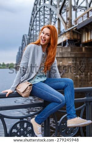 Redhead casual girl posing near river bridge - stock photo