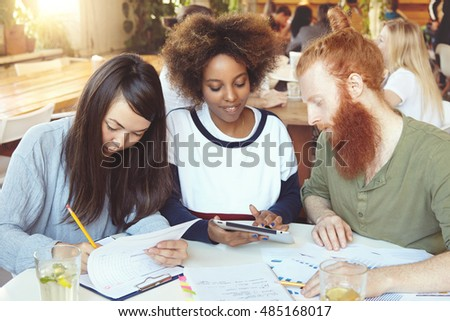Redhead Caucasian male and his Asian and African female college mates preparing for classes of Economics, sitting at cafe. Dark-skinned student girl showing something to her bearded friend on tablet