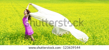 redhead curly Nice girl going in a green and yellow rapeseed field - Symbol of lightness, softness, tenderness, windiness, flight, dreaming, rest and relaxation in the fresh air - stock photo