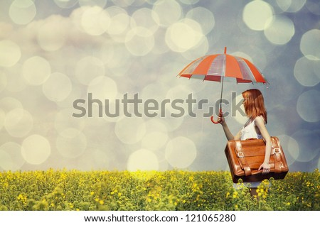 Redhead enchantress with umbrella and suitcase at spring rapeseed field. - stock photo