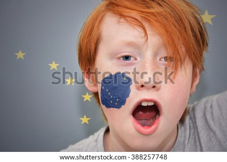 redhead fan boy with alaska state flag painted on his face.  - stock photo
