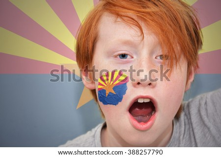 redhead fan boy with arizona state flag painted on his face.  - stock photo