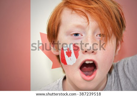 redhead fan boy with canadian flag painted on his face. on the canadian  flag background - stock photo