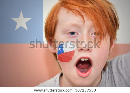redhead fan boy with chilean flag painted on his face. - stock photo