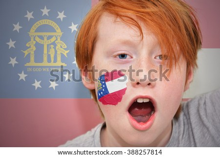 redhead fan boy with georgia state flag painted on his face.  - stock photo