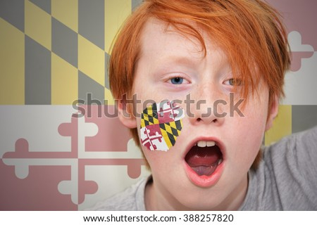 redhead fan boy with maryland state flag painted on his face.  - stock photo