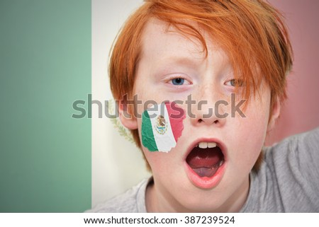 redhead fan boy with mexican flag painted on his face. - stock photo