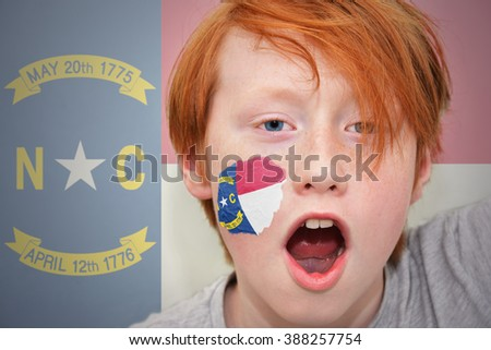 redhead fan boy with north carolina state flag painted on his face.  - stock photo