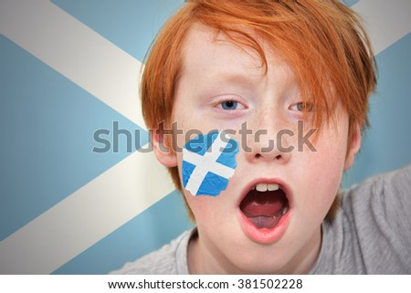 redhead fan boy with scottish flag painted on his face. on the scottish  flag background - stock photo