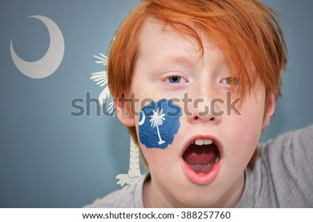 redhead fan boy with south carolina state flag painted on his face. - stock photo