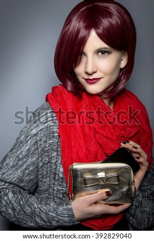 Redhead fashion model holding a stylish cell phone purse accessory.  The purse is a case for the mobile phone.