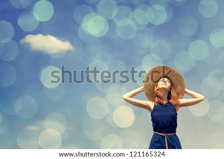 Redhead girl at spring blue sky background. Photo with bokeh at background. - stock photo