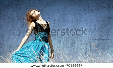 Redhead girl at windy field. Photo in old color image style. - stock photo