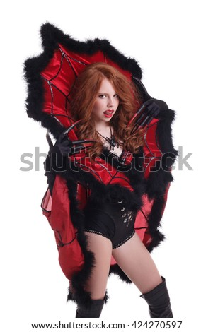 Redhead girl dressed as Spider Queen licks her lip