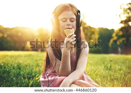 redhead girl eating ice cream and listening to music in headphones - stock photo