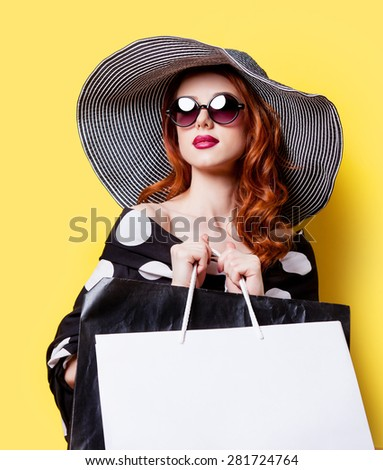 Redhead girl in black dress and hat with shopping bags on yellow background - stock photo