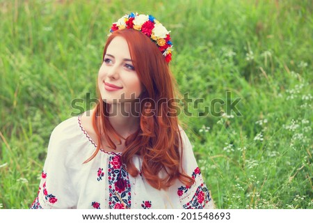 Redhead girl in national ukrainian clothes on the green grass.