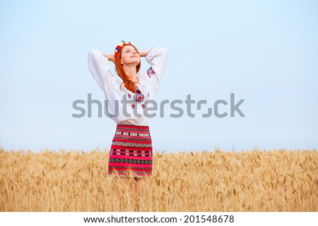 Redhead girl in national ukrainian clothes on the wheat field. - stock photo