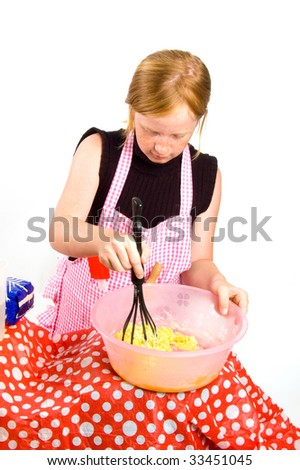 redhead girl is making pancake dough isolated on white