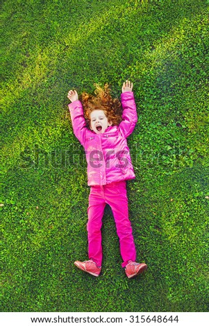 Redhead girl lying on the green grass in park. Season sale, advertising concept. - stock photo