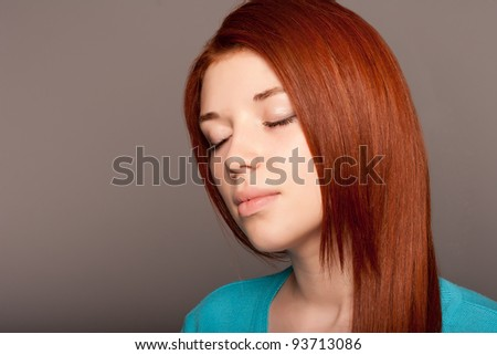 Redhead girl on a gray background