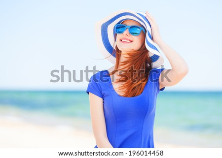 Redhead girl on the beach in spring time. - stock photo