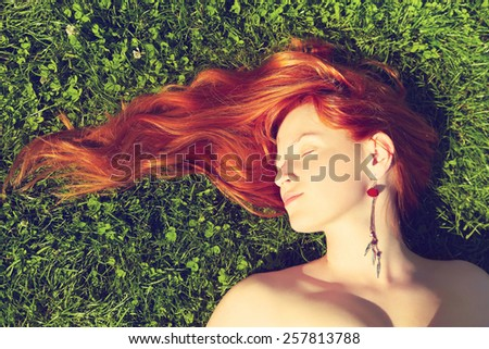 redhead girl relaxing lying on the grass. woman relaxation outdoor. photo with artistic effect. vintage toning. film retro style - stock photo