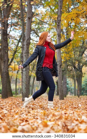 redhead girl run with leaf bouquet in city park, fall season