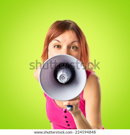 Redhead girl shouting with a megaphone over green background  - stock photo