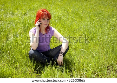 Redhead girl talking on the phone in a forest