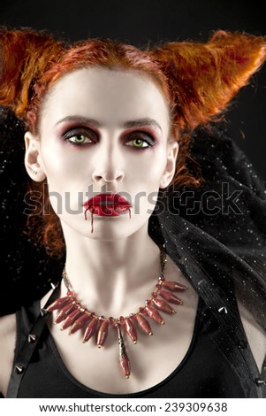 Redhead girl vampire-demon. sexy woman in the studio. - stock photo