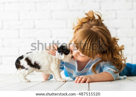 Redhead girl with a cocker spaniel puppy