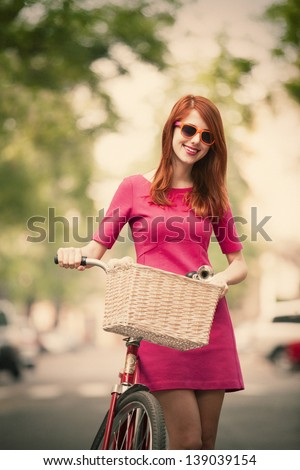 Redhead girl with bike on the street - stock photo