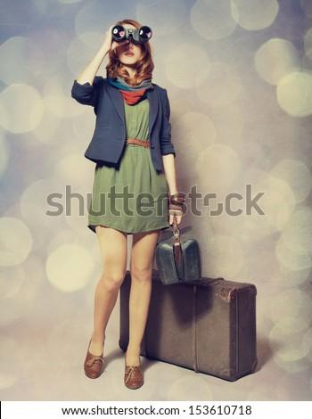 Redhead girl with binocular standing near the big suitcase - stock photo