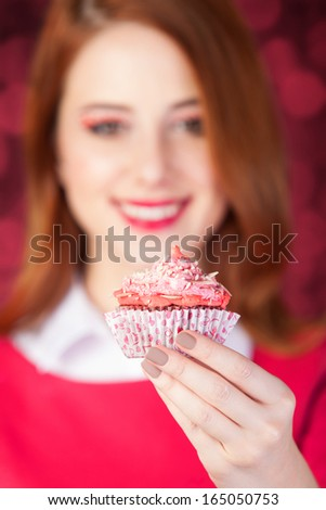 Redhead girl with cake. Photo red background with bokeh.