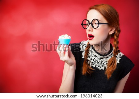 Redhead girl with cupcake on red background