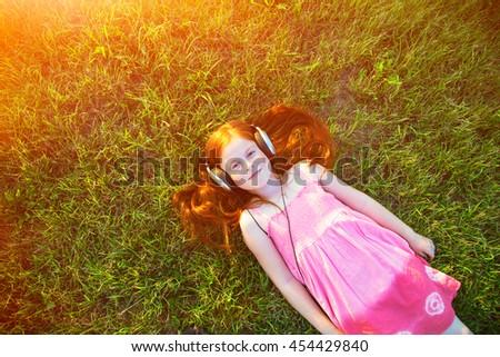 redhead girl with headphones listening to music - stock photo