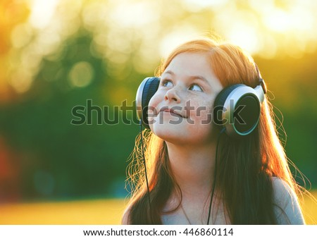 redhead girl with headphones listening to music. space for text - stock photo